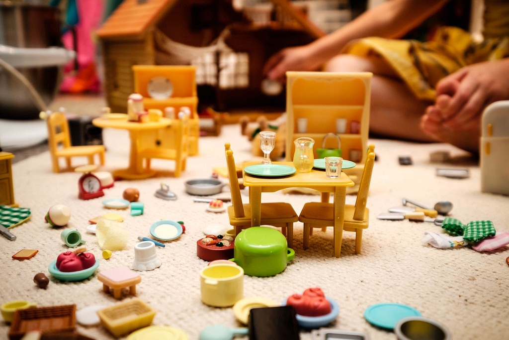 A jumble of toy kitchen items strewn on a carpet.