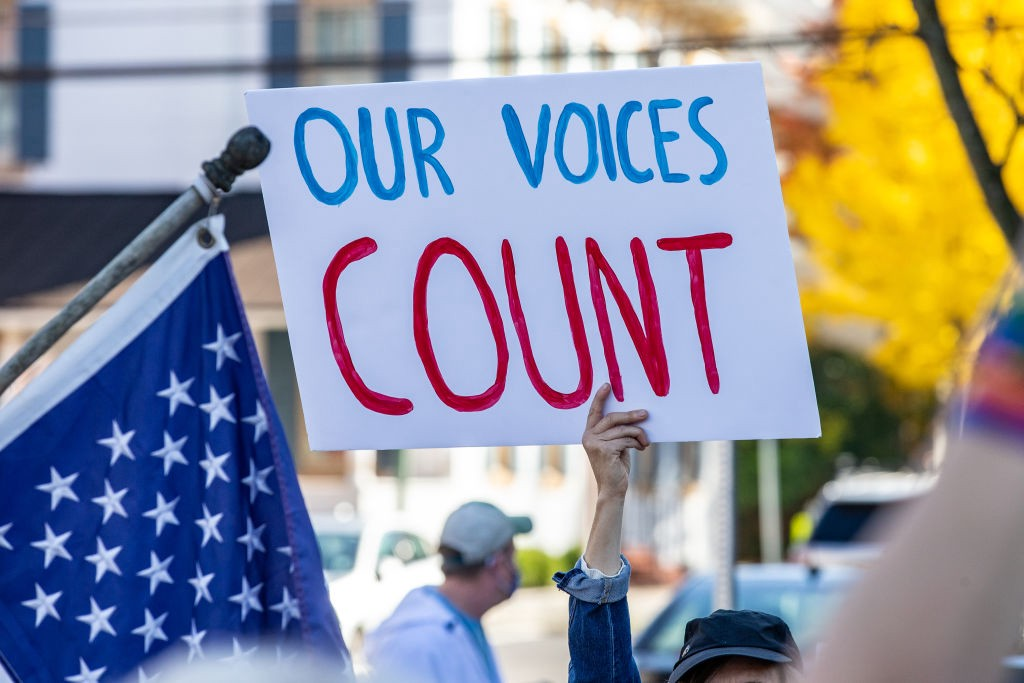 """Protestor holding a sign that says """"OUR VOICES COUNT."""""""