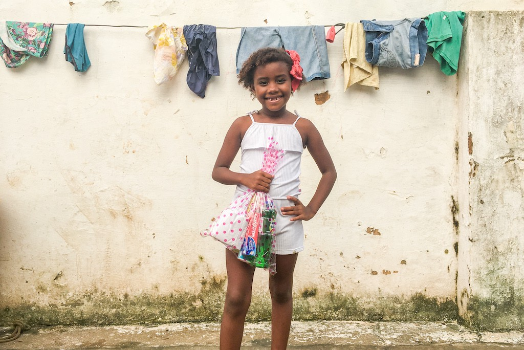A Afro-Brazilian girl stands in front of a off-white wall, holding a bag of hygiene supplies.