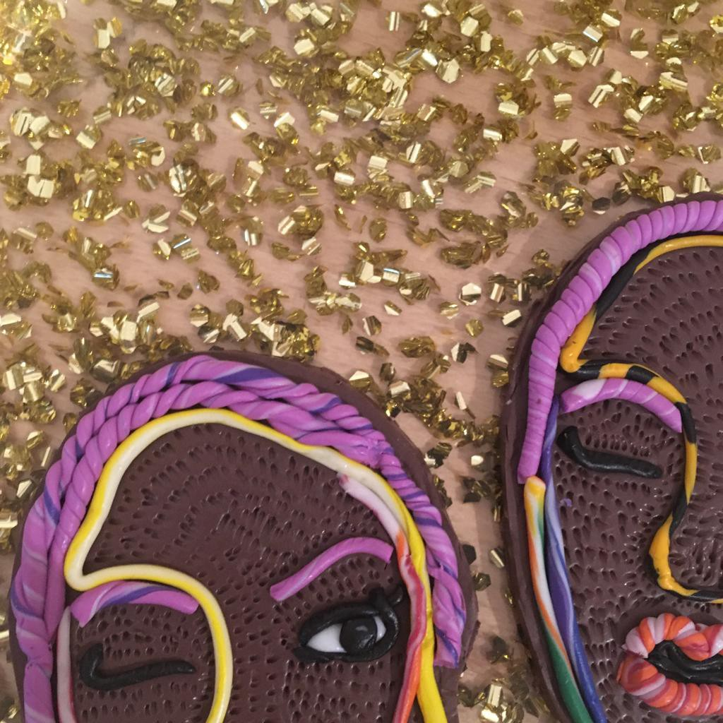 Two brooches of Black women on top of a gold glitter background