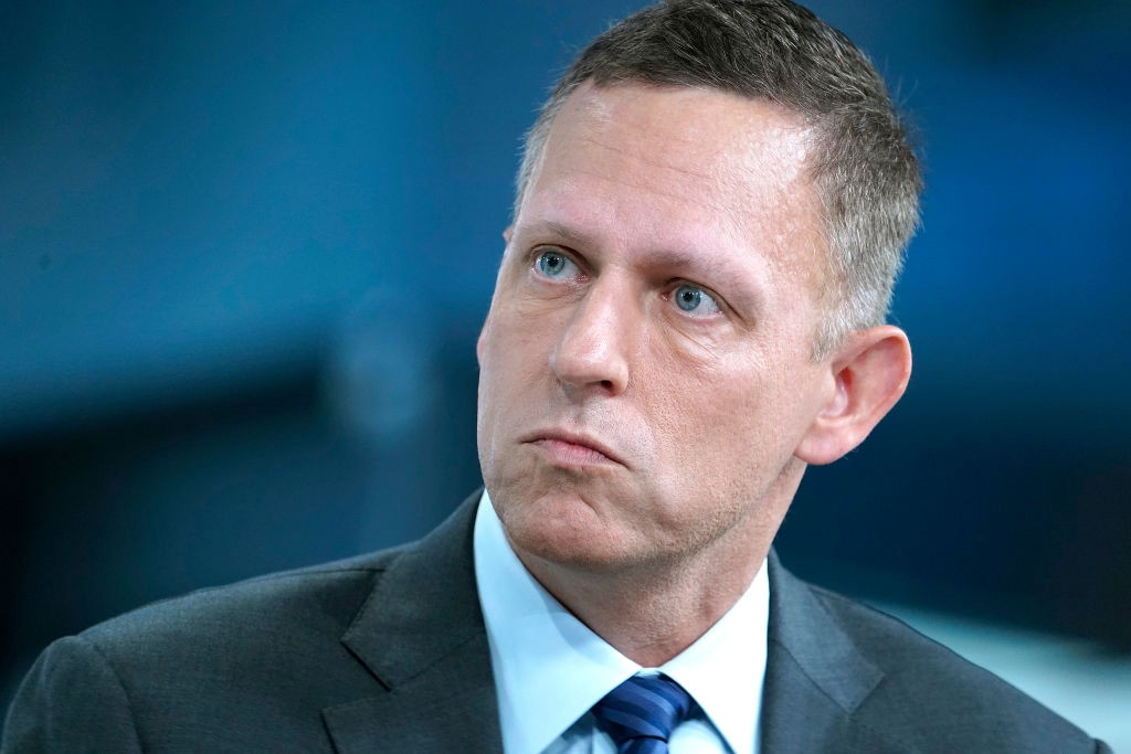 Closeup photo of Peter Thiel wearing a suit during an interview.