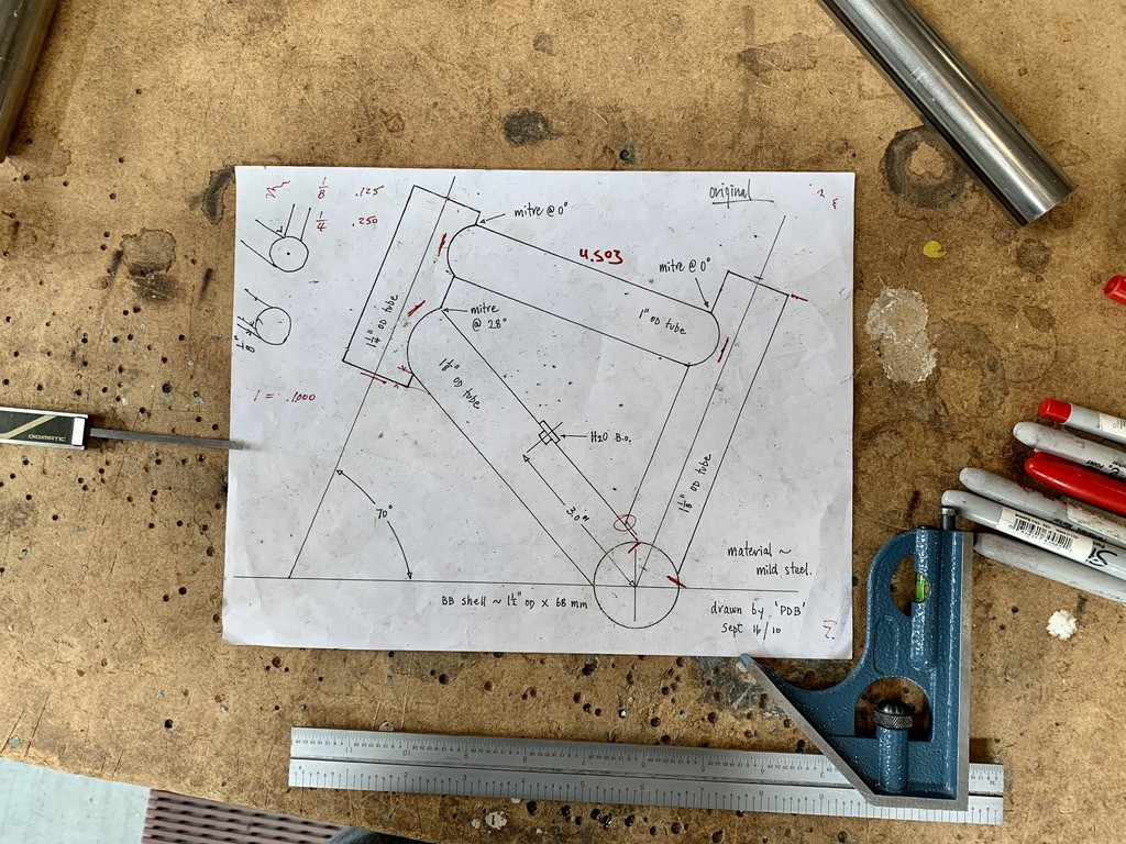 A schematic of a miniature bike frame sitting on a workbench