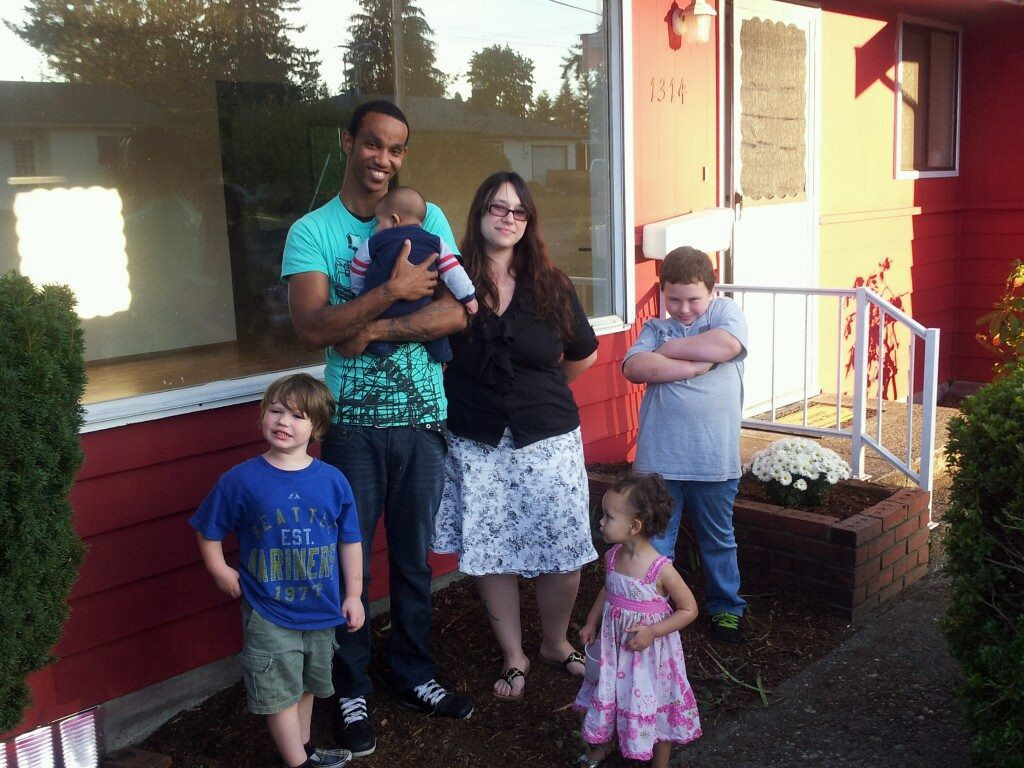 A photo of young parents and their four children standing outside a home. They are smiling at the camera.