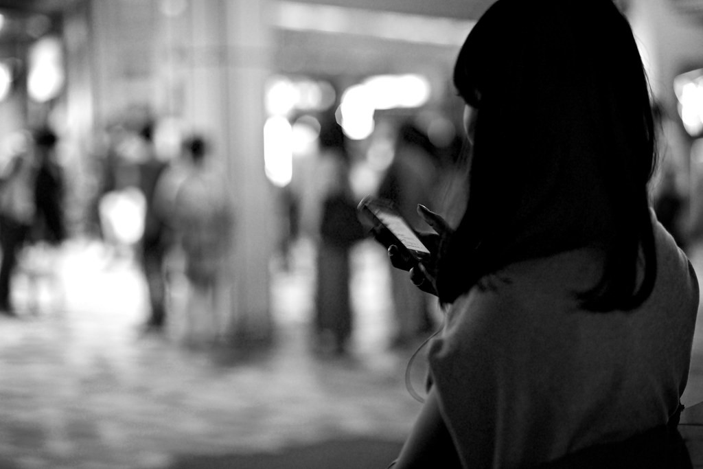 A black and white photo of a black-haired woman on her phone in a busy city street.