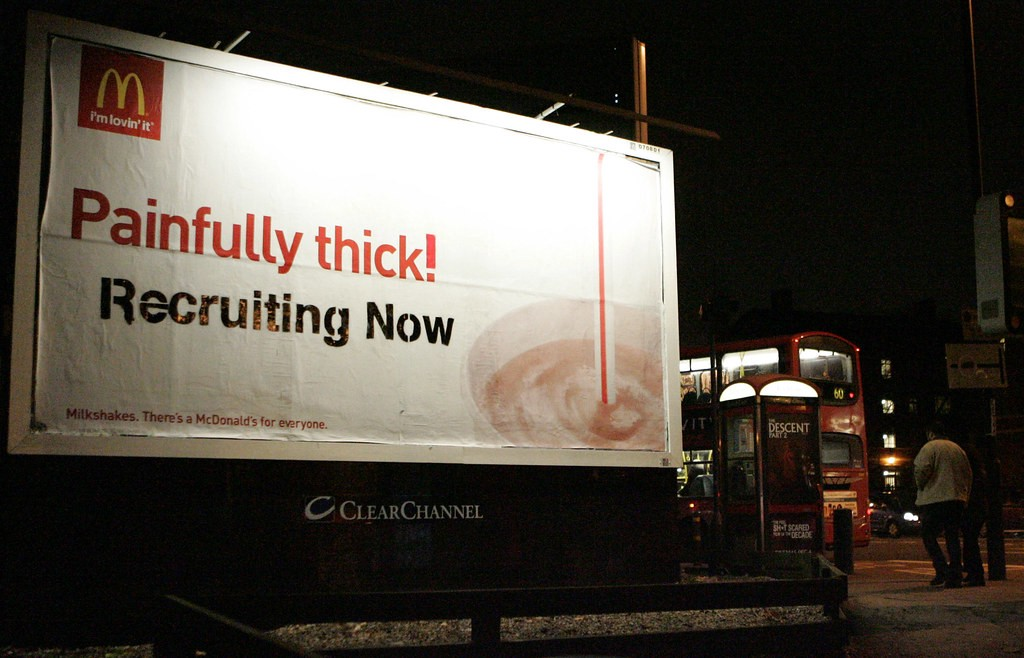 """Billboard featuring a McDonald's milkshake and the slogan """"Painfully Thick"""", edited to add """"Recruiting Now"""" underneath"""
