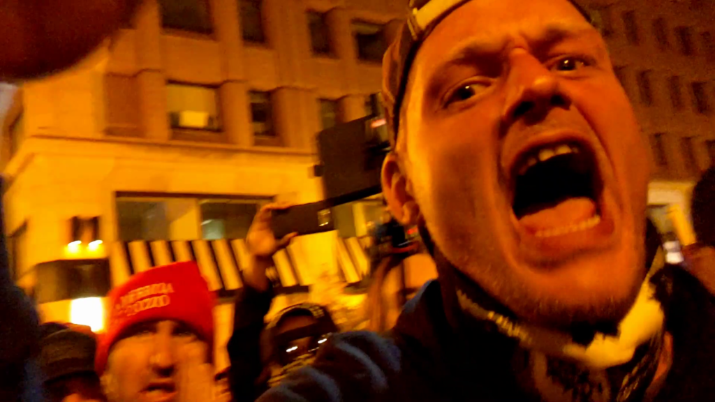 Night on a city street. A man screams furiously at the camera. Behind him, a man with a red MAGA beanie stands out of focus