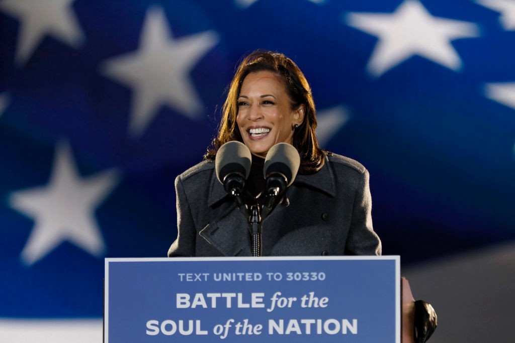 Kamala Harris giving a speech, she is smiling widely.