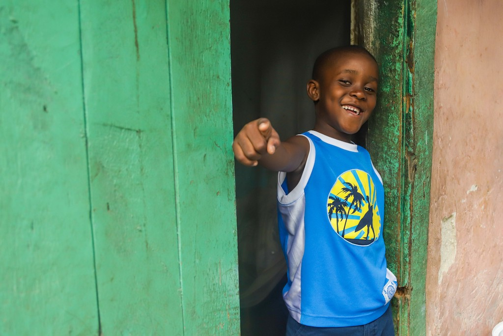 A Haitian boy stands in a green doorway wearing a blue t-shirt and smiling and posing, pointing his finger at the camera.