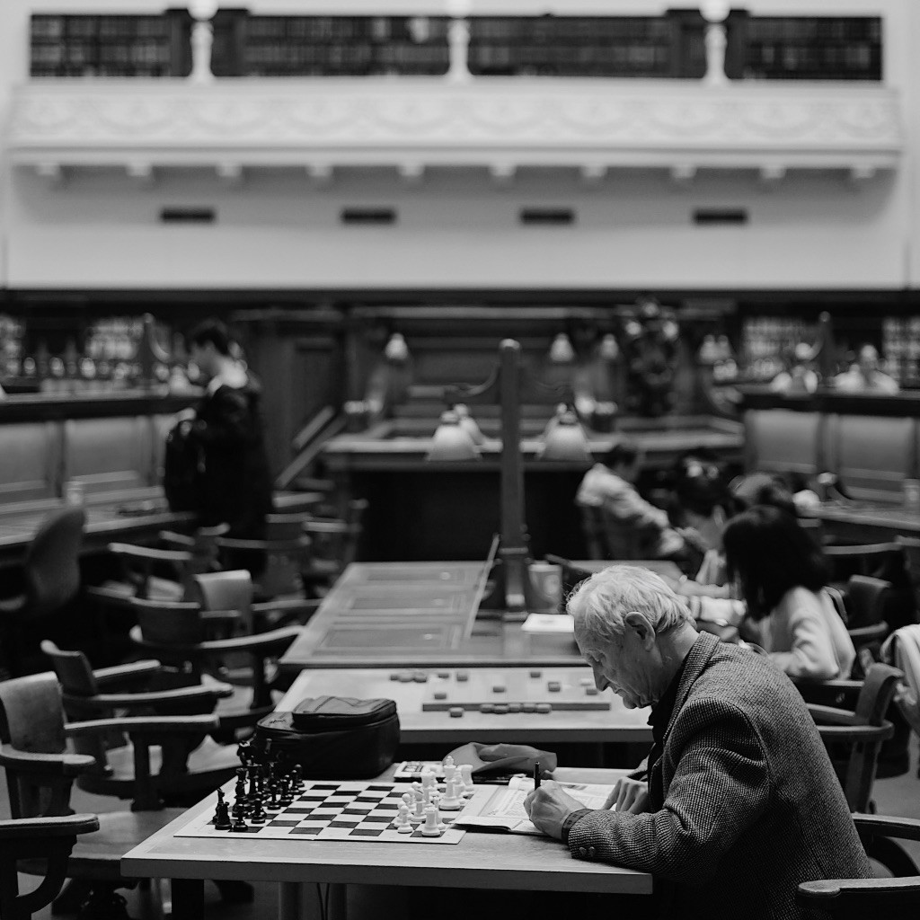 Man sitting at table in a library with notebook and chessboard.