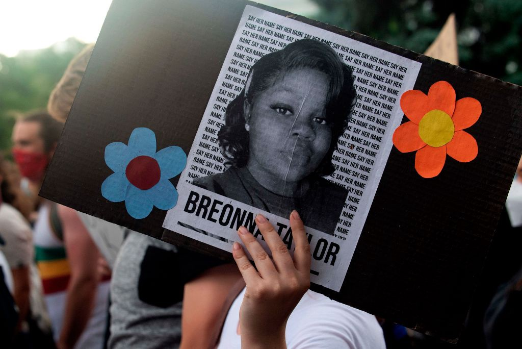A photo of Breonna Taylor on a sign that a protestor is holding at a rally in Denver, Colorado.