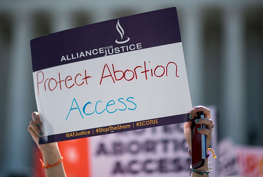 """A woman holding up a sign that says """"Protest Abortion Access."""""""