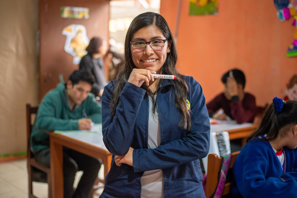 Pamela wears glasses and a blue jacket, standing and smiling in her classroom as students work at desks behind her.