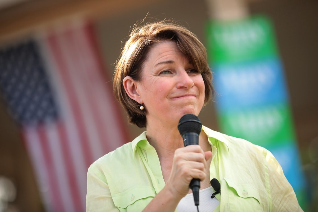 Amy Klobuchar at campaign rally on front lawn of a residence.