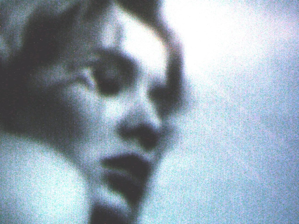 A grainy low-res photo of a woman with her eyes closed, seemingly resting her head on a pillow.