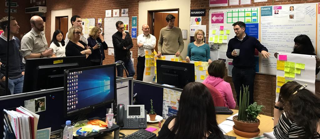 A group of JRF team members stood up in an open plan office presenting a project show and tell to colleagues.