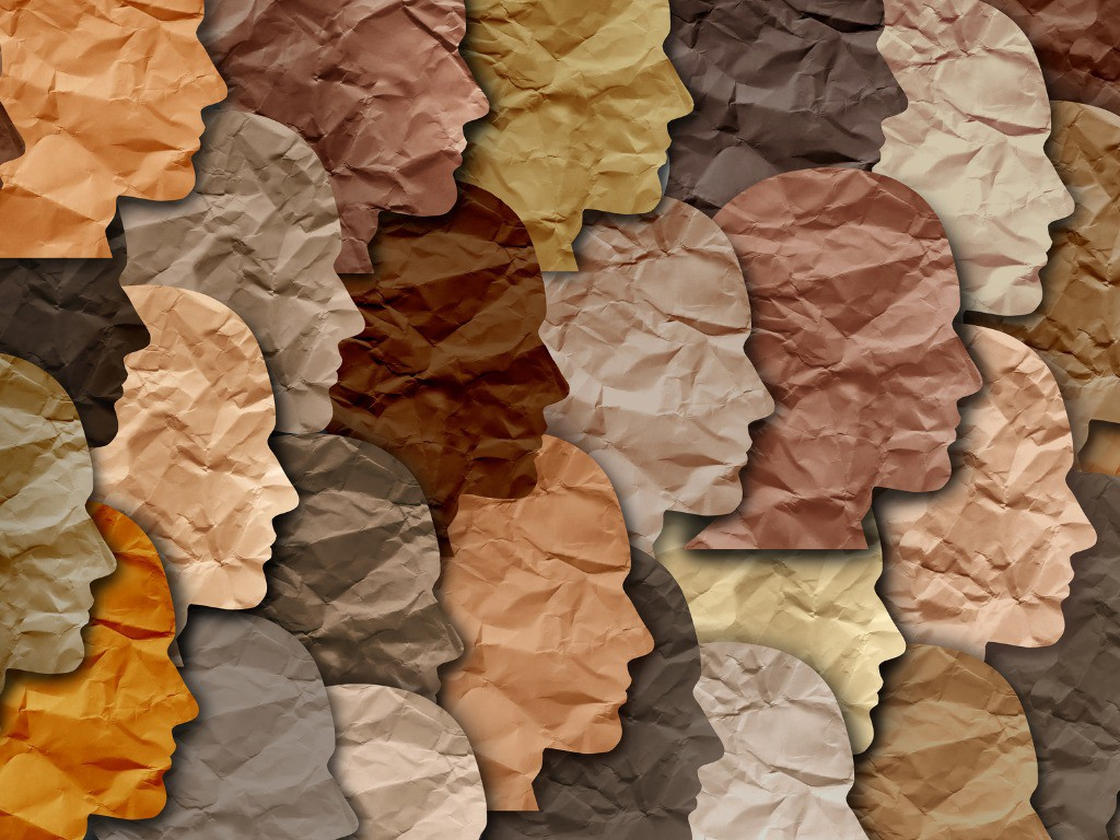 Crinkled paper silhouettes of people's faces overlap with one another in different shades of color representing a wide range of skin tones.