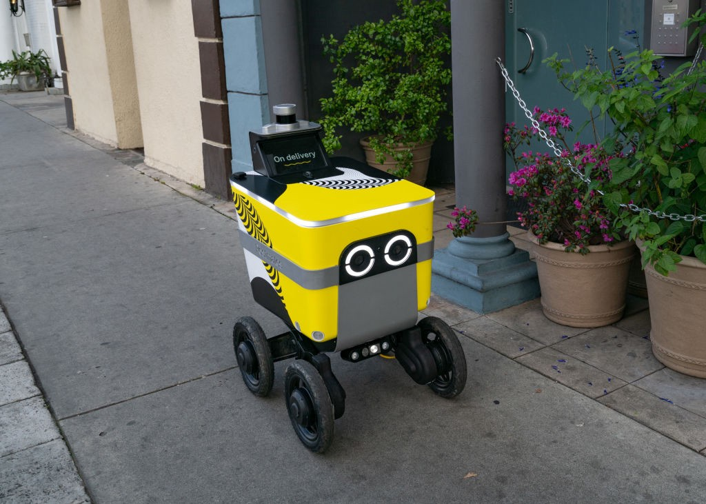 A photo of a Postmates food delivery robot going down a sidewalk.