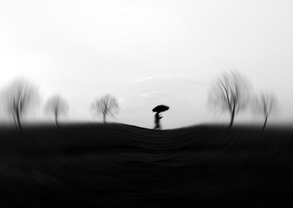 Blurry black and white image of a person walking holding an umbrella with some bare trees.