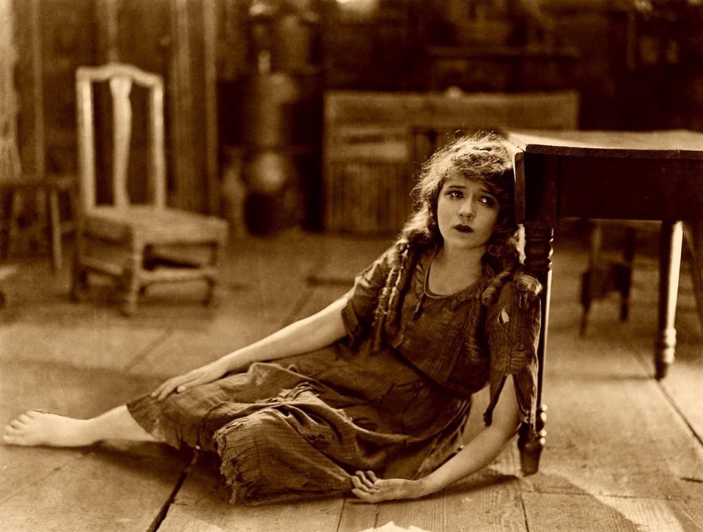Mary Pickford from the Silent Era, sitting collapsed on the floor.