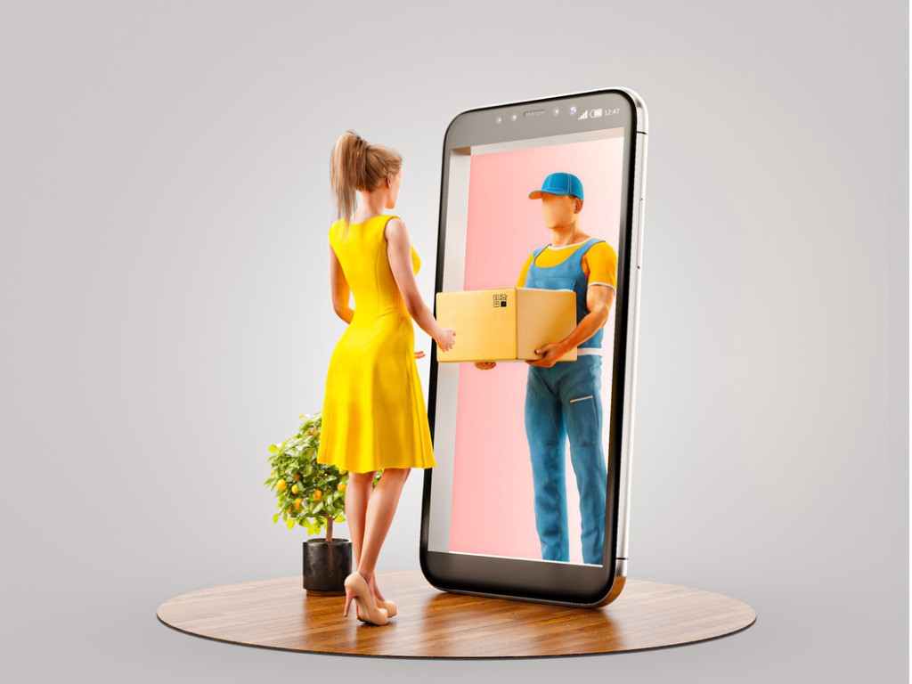 A Barbie figurine facing a Ken figurine inside of a phone on top of a wooden table.
