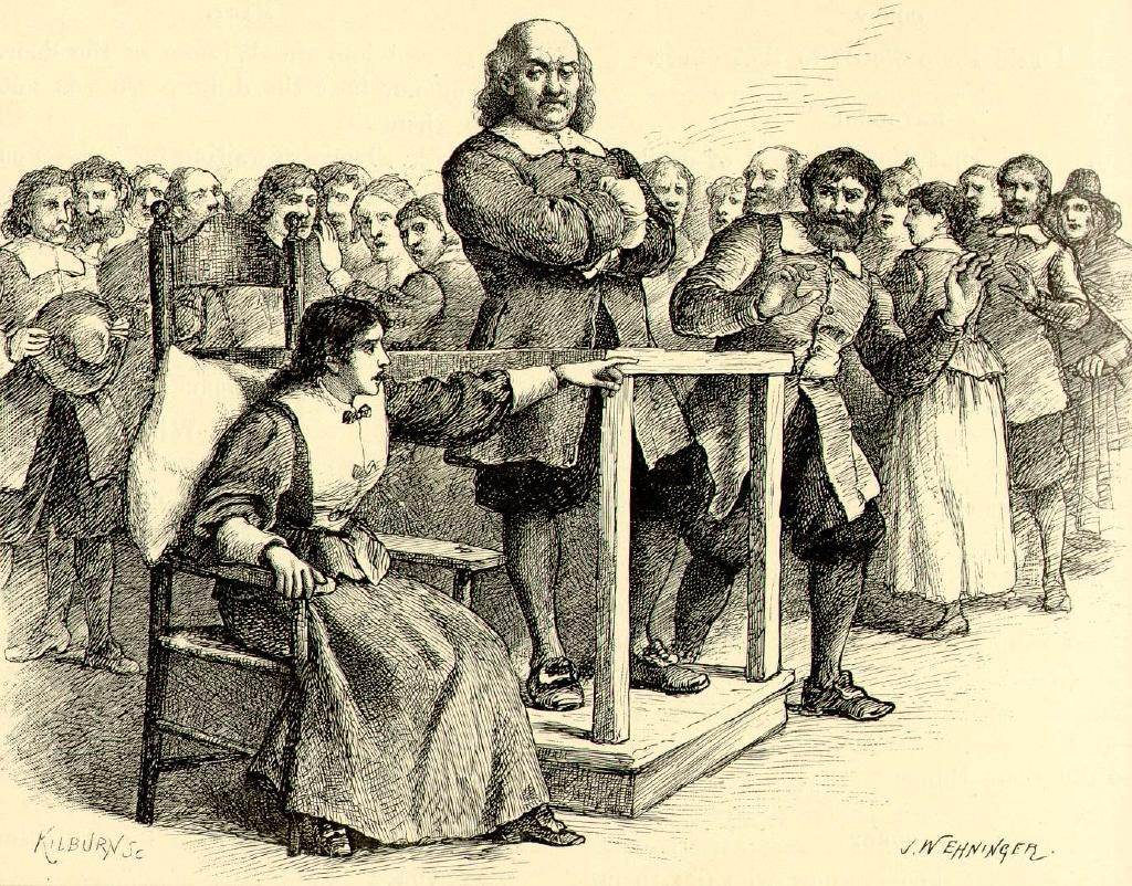 Salem witch trials: A man stand defiantly on trial as a woman sitting next to him points into the stunned crowd