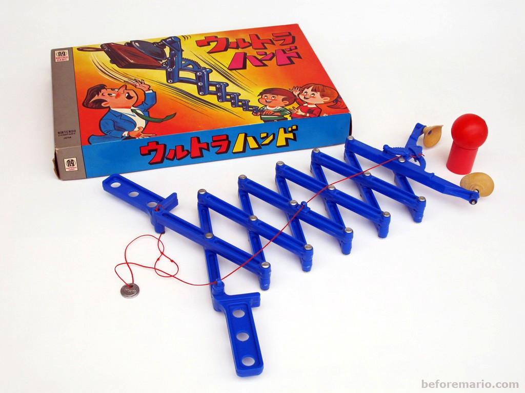 A plastic toy with two handles that can be pushed or pulled to extend or retract the two rubber clamps grasping an object.