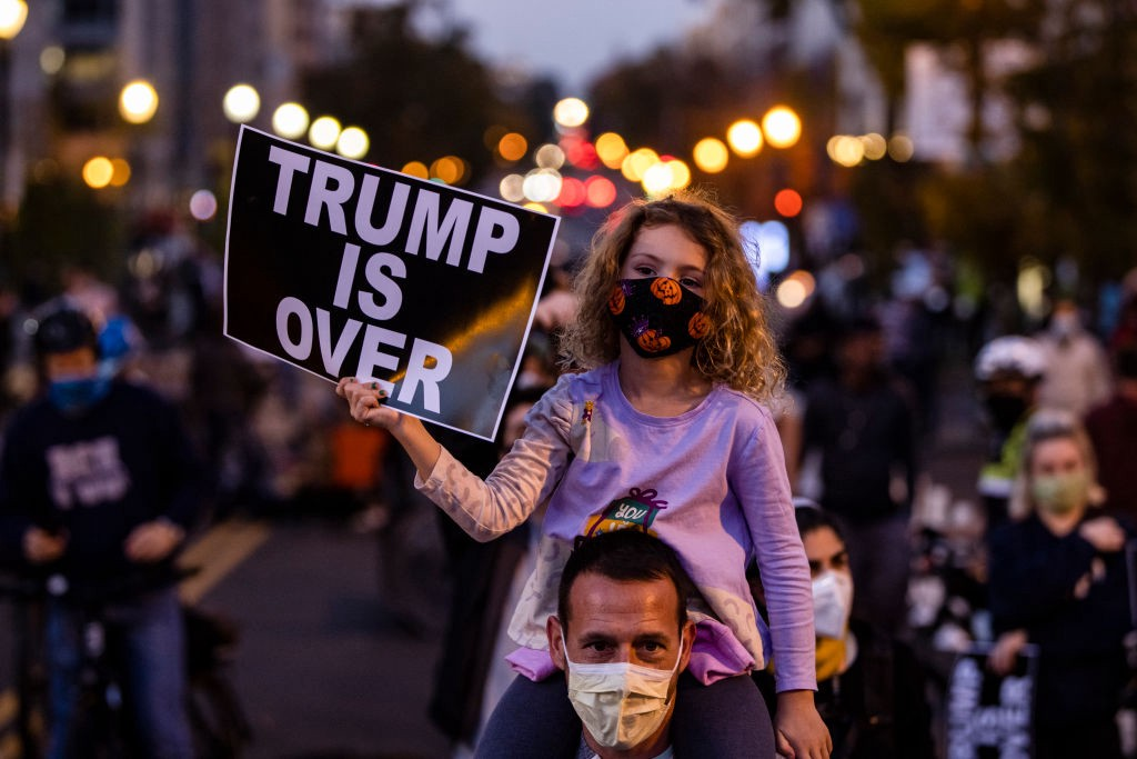 """A young girl wearing face mask sits on top of her dad's shoulders at a protest, holding a sign that says """"TRUMP IS OVER."""""""