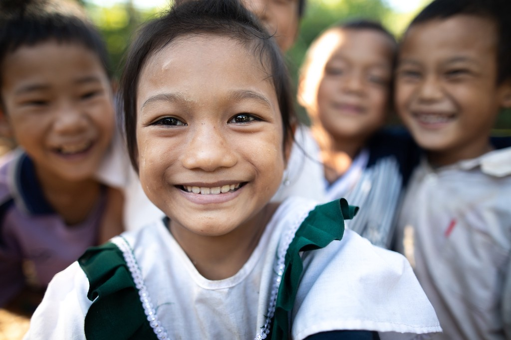 Tarchanee, a young Thai girl, is smiling and standing outside wearing a green and white shirt. Her friends are behind her.