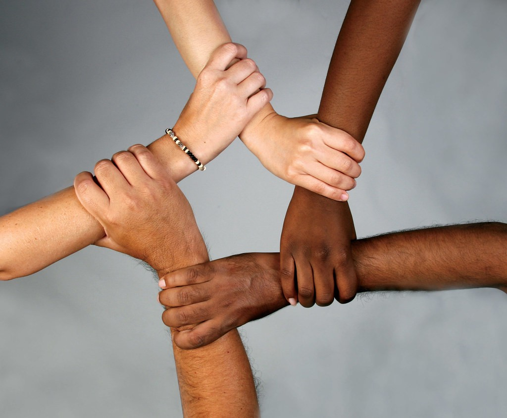Five hands of people from varying races holding each other's wrists forming a pentagon shape in the middle.
