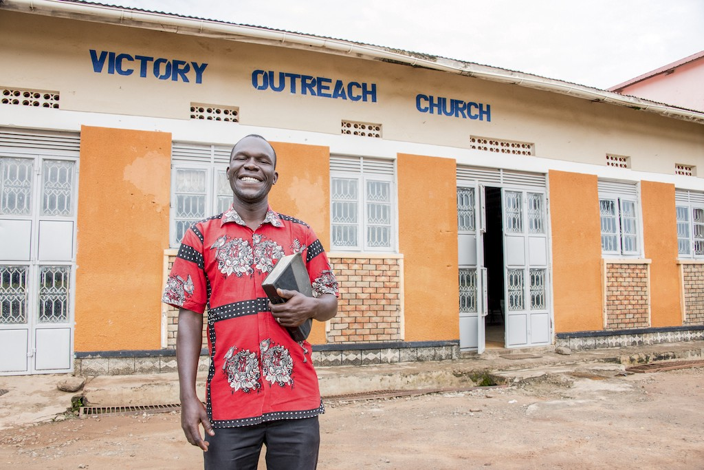 A man in a red patterned shirt stands smiling and holding a Bible in front of Victory Outreach Church, a yellow building.