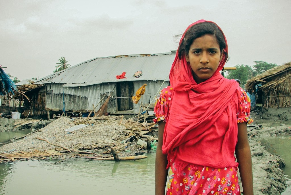 Aduri is wearing a red dress and headscarf and standing in front of her collapsed home.