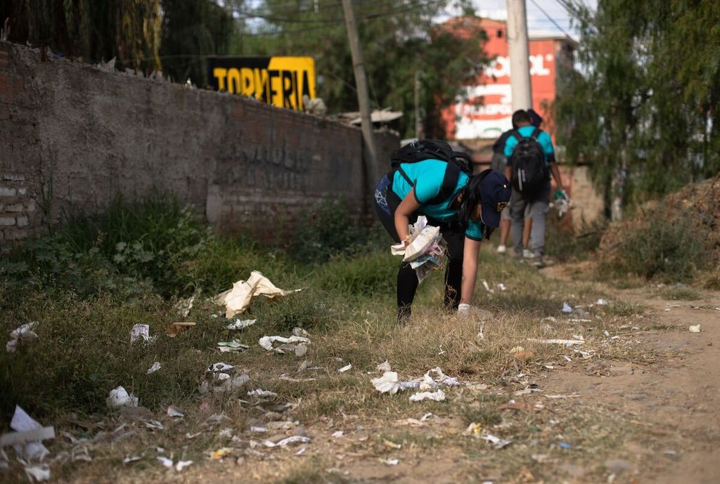 In Bolivia, teenagers wearing blue t-shirts are picking up trash. There is a brick wall to one side.
