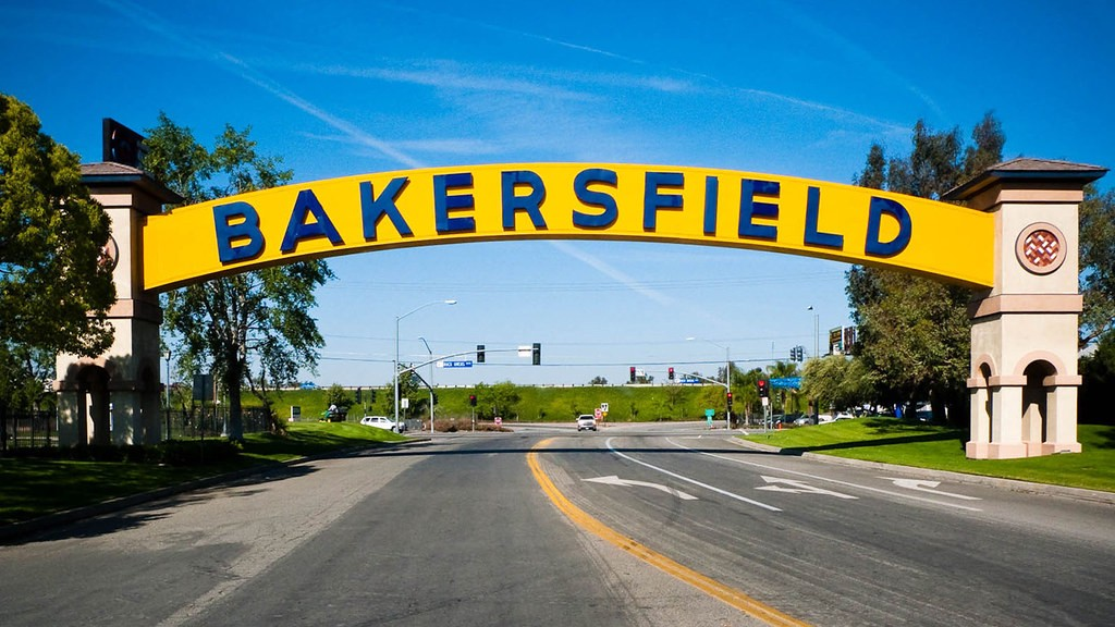 Bakersfield sign arced over street with freeway behind.