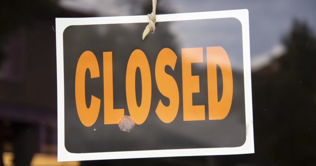 Closed sign hanging in business window by a string