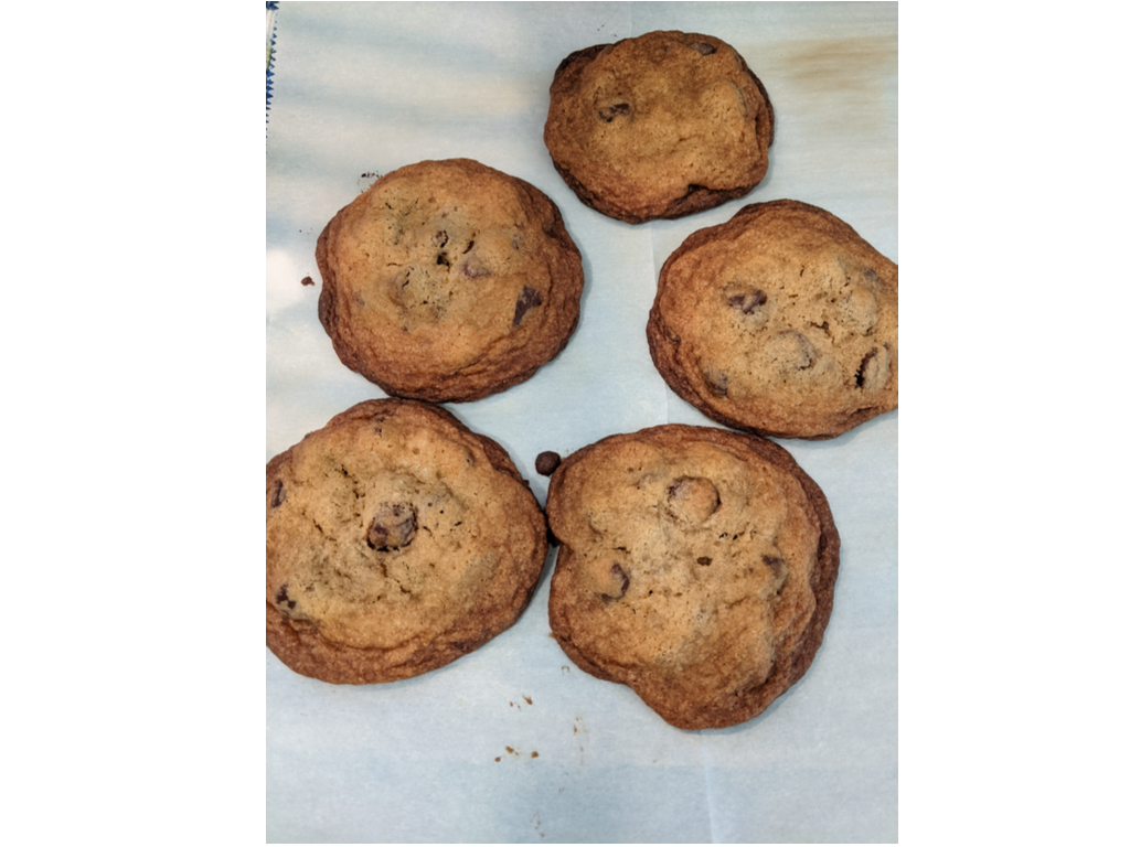 Baked chocolate chip cookies resting on parchemnt paper.