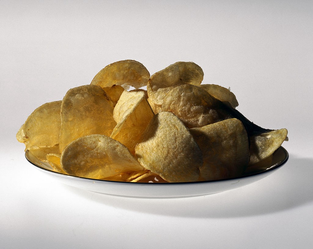 A dish overflowing with potato chips on a white background.