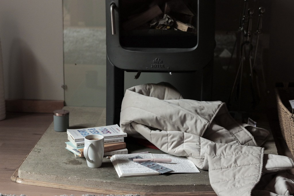 A fireplace log burner, blanket, books, journal, pen and cup of tea