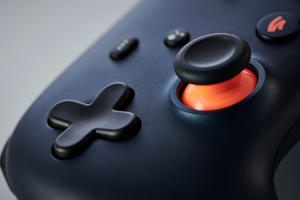 Very zoomed-in photo of a Google Stadia controller, the D-pad and analogue stick with orange highlight.