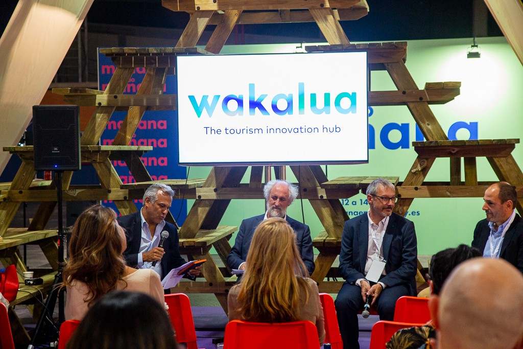 4 Male panelists seated in front of screen with logo wakalua