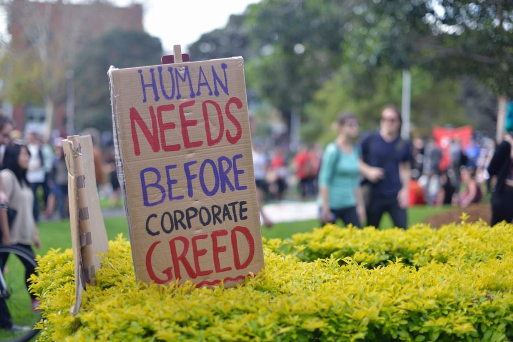 """A banner reads """"Human needs before corporate greed"""""""