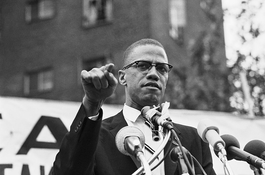 An archival black and white photo of Malcolm X giving a speech.