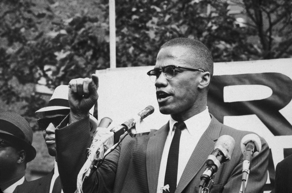 Malcolm X giving a speech at a rally.