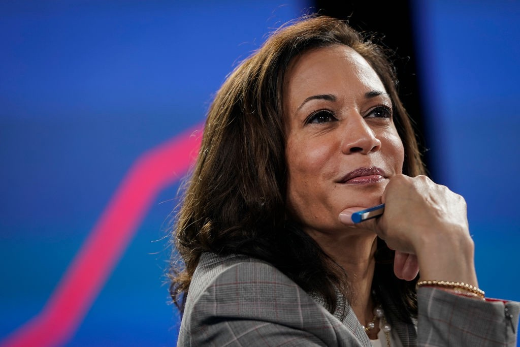 Closeup photo of Kamala Harris with a slight smile on her face, hand on chin.