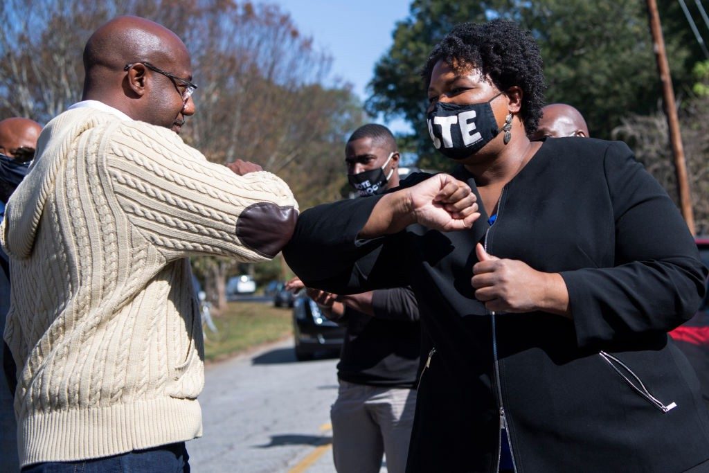 Reverend Raphael Warnock and Stacey Abrams bump elbows.