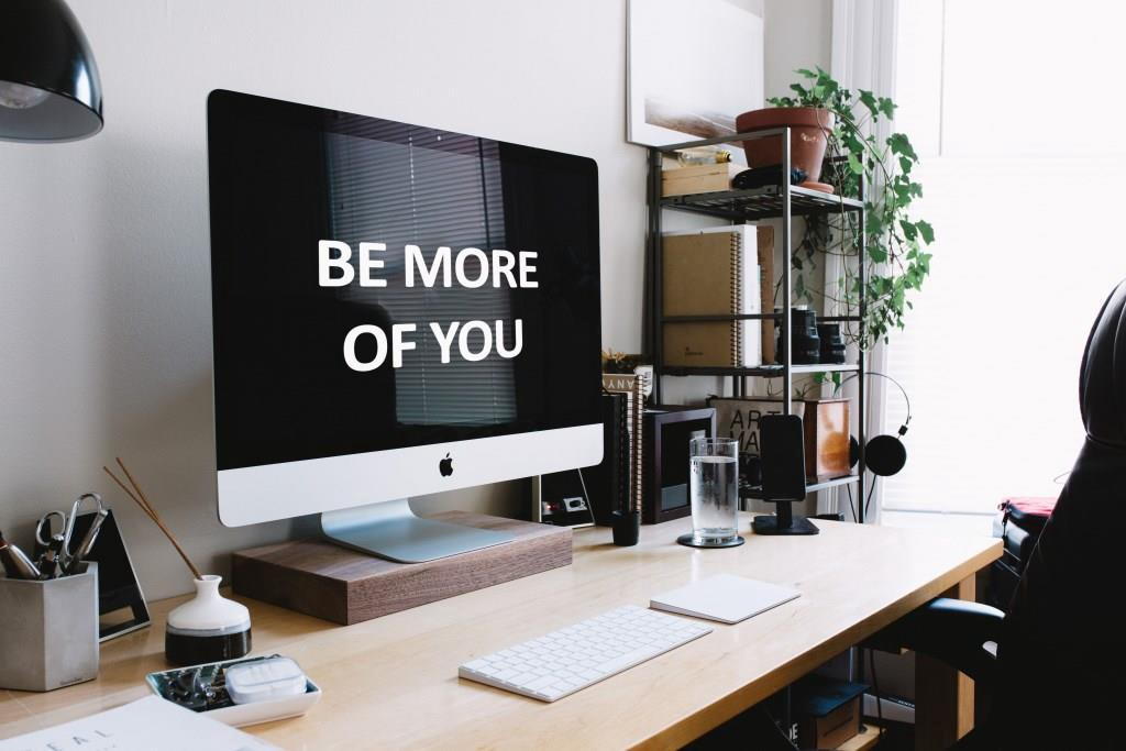 """Computer desk with """"Be More of You"""" on computer screen"""
