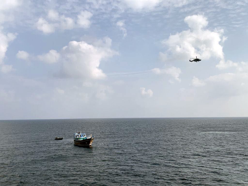 An image of Royal Marines approaching the dhow with the Wildcat helicopter flying overhead