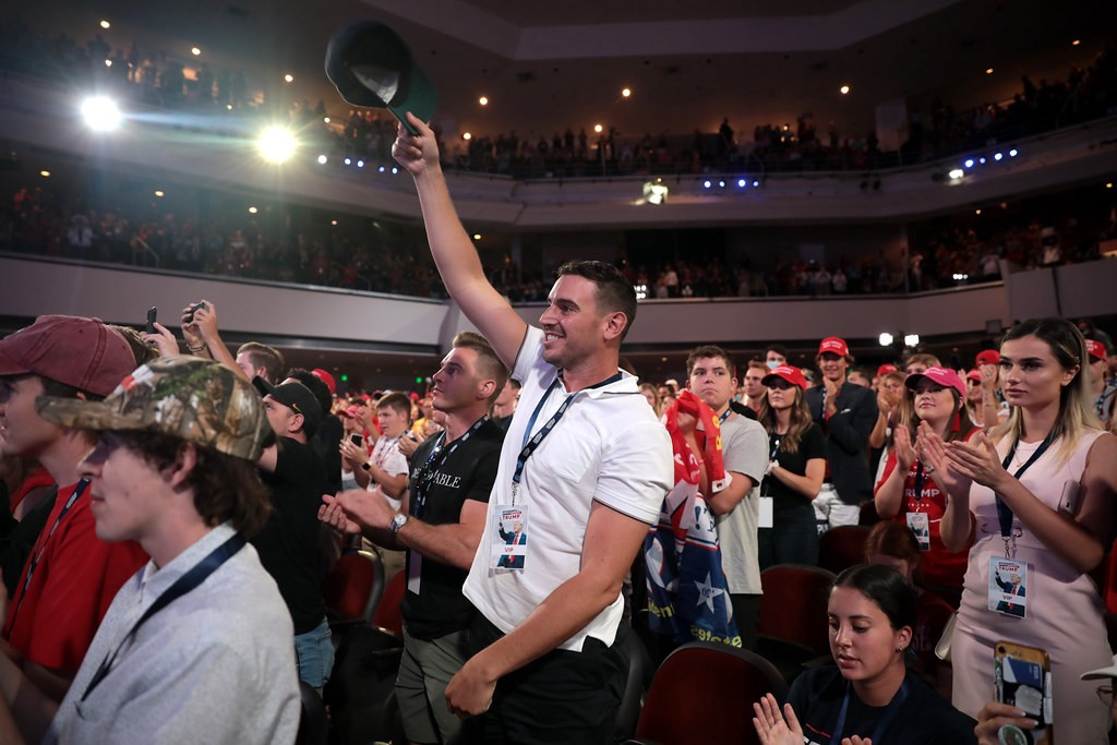 An auditorium fullof young Trump supporters. A muscular man in a white polo shirt holds his black cap aloft, grinning