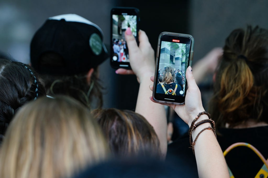 A photo of protestors recording videos on their phones.