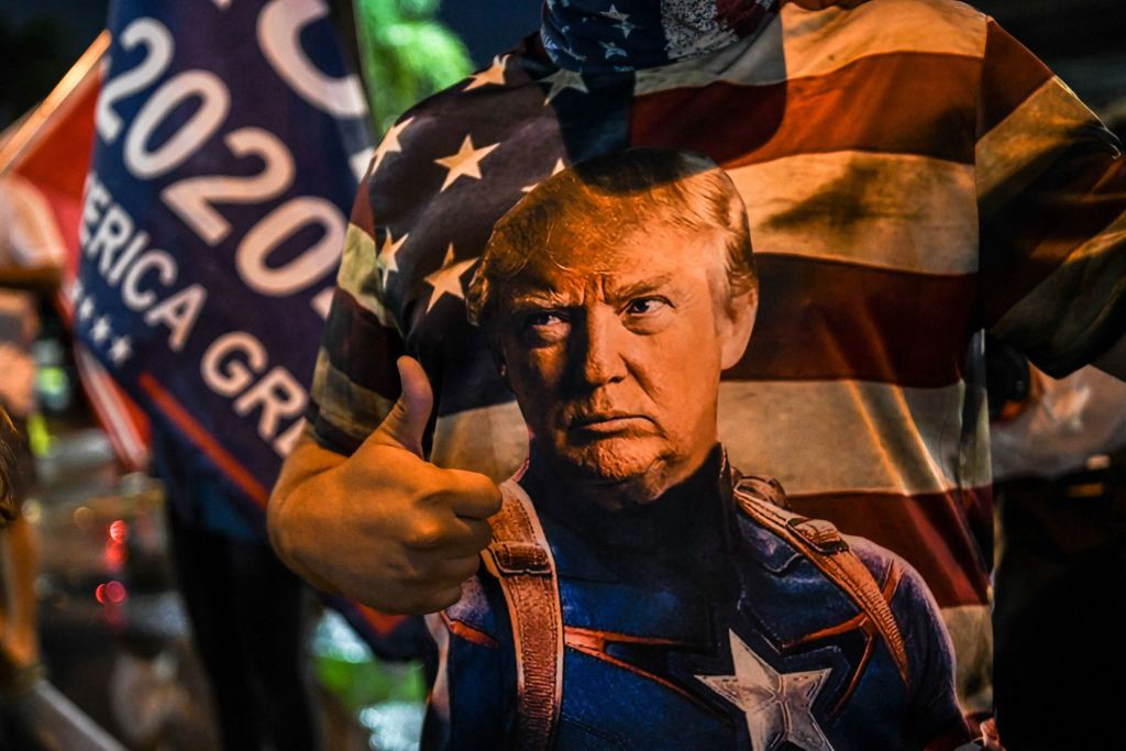 Trump supporter wears a shirt that has Trump as Captain America in front of American flag.