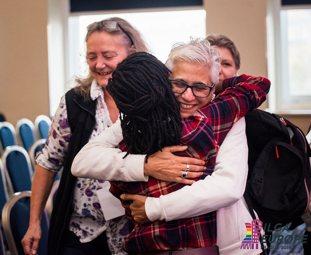 Two conference participants hug warmly, with big smiles